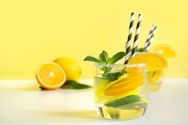 Summer refreshing cocktail with lemon, orange, mint and ice in glass on yellow. tropical concept.