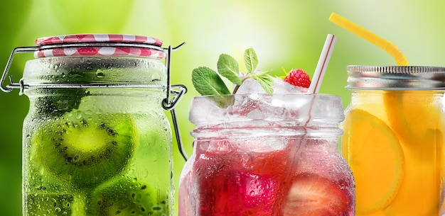 Летние освежающие коктейли лимонад из свежих фруктов и ягод в стеклянных банках с капельками крупным планом