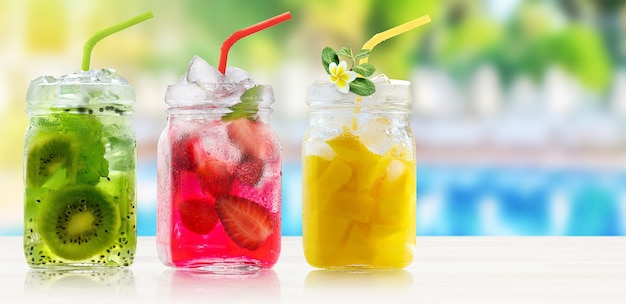 Summer refreshing cocktails with ice and  straws on bar counter on swiming pool background