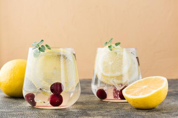 레몬과 체리를 곁들인 여름 상쾌한 차가운 칵테일-테이블에 안경에 하드 셀저