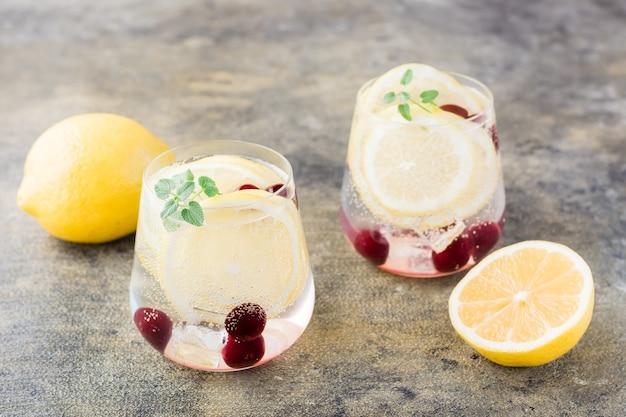 레몬, 레몬 밤, 체리가 들어간 여름 상쾌한 차가운 칵테일-테이블 위의 안경에 담긴 하드 셀처