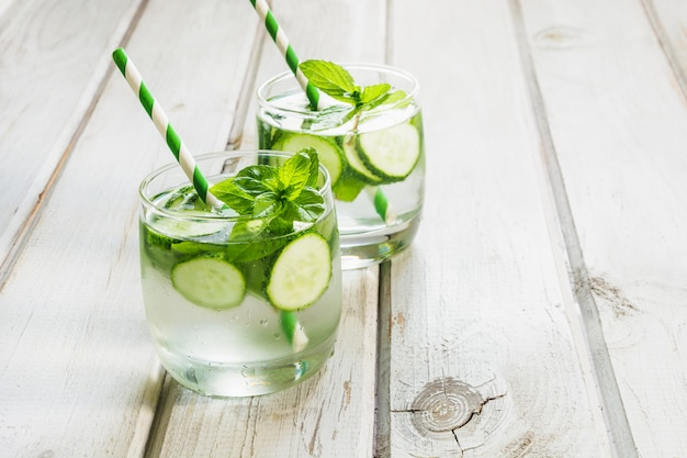Summer refreshing detox cocktail. water with cucumber, mint and ice in glass on white wooden board.