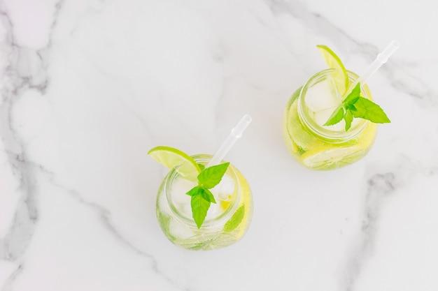 Летний освежающий детокс-коктейль. вода с лимоном, мятой и льдом в очках на белом мраморном фоне.
