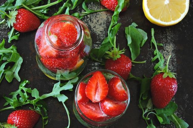 Summer refreshing detox drink strawberry lemon arugula.