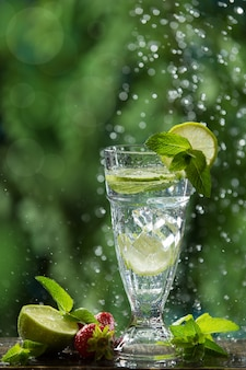 Летний освежающий напиток в высоком стакане с лаймом, мятой и льдом, брызгами воды
