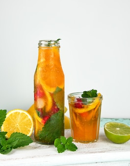 Summer refreshing drink lemonade with lemons, cranberry, mint leaves, lime in a glass bottle