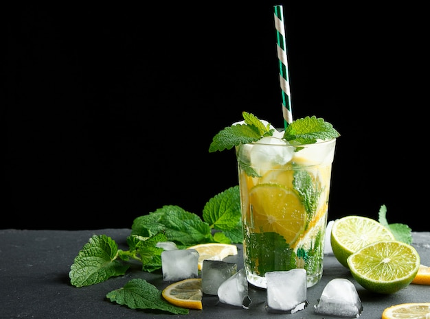 Summer refreshing drink lemonade with lemons, mint leaves, ice cubes and lime in a glass