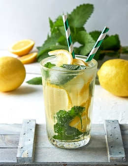 Summer refreshing drink lemonade with lemons, mint leaves, lime in a glass