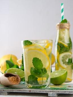 Summer refreshing drink lemonade with lemons, mint leaves, lime in a glass