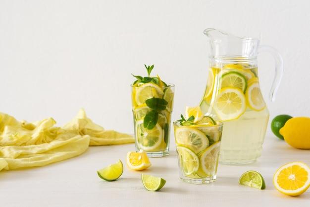 레몬, 라임, 민트의 여름 상쾌한 음료, 레모네이드와 유리잔, 감귤 조각이 든 주전자