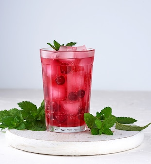 Summer refreshing drink with berries of cranberries and pieces of ice