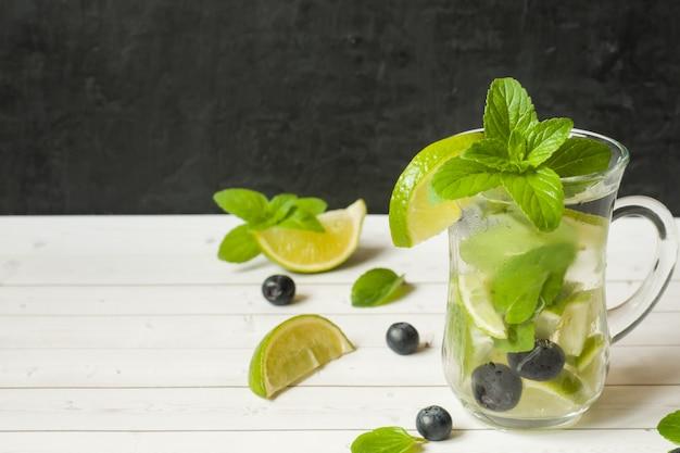 夏の爽やかな飲み物は、ライムフレッシュミントブルーベリーアイスと共にレモネードまたはカクテルモヒートを飲みます。 Premium写真