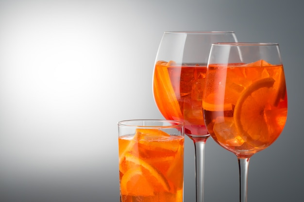 Summer refreshing faintly alcoholic cocktail aperol spritz in a glass glass with ice set