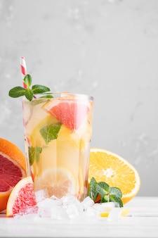 明るい背景にミントと夏のさわやかなレモネード。軽いキーで柑橘系のカクテルのグラス。閉じる。オレンジ、レモン、グレープフルーツの夏のビタミンカクテル。