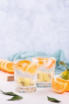 오렌지와 키위 과일 근접 촬영 정물과 함께 여름 상쾌한 무알콜 칵테일. 감귤류와 탄산수, 건강한 생활 방식, 알코올 개념 없이 생활하는 여름 목테일
