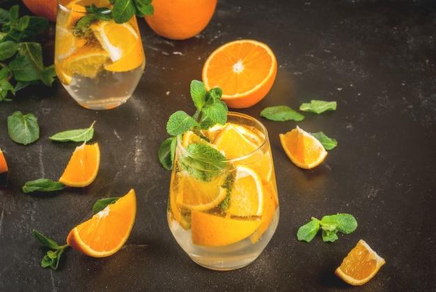 夏のさわやかなオレンジ色の飲み物デトックスダイエットレモネードのバリエーション新鮮なオレンジとミントの部分とミネラルウォーター黒い石のコンクリートテーブル水平に