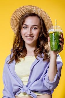 여름 다과. 차가운 음료. 신선한 칵테일 플라스틱 컵과 젊은 여자 무알코올 음료입니다. 해독 레모네이드