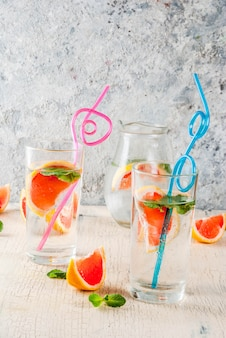 Summer refreshment detox water drink with pink grapefruit and fresh mint, spa fruit water, lemonade or jin tonic cocktail, light concrete background