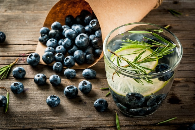 Summer refreshment diet drinks. infused detox water with rosemary, lime and blueberries. rustic wooden old table  copyspace
