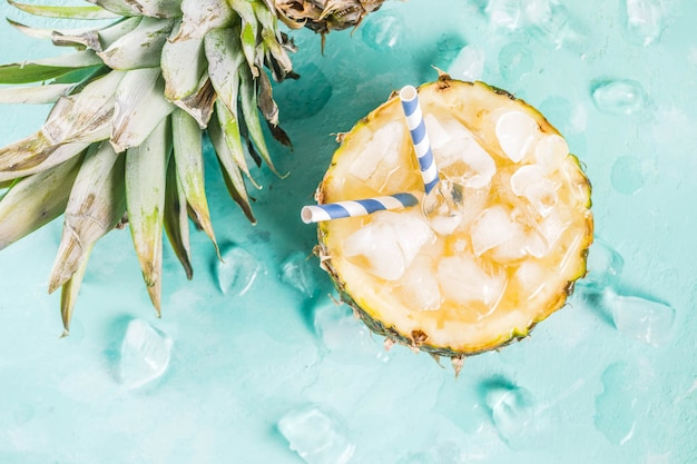Summer refreshment drink concept tropical pineapple cocktail or juice in pineapple with ice