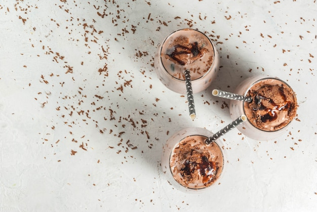 Summer refreshment drinks. chilled iced chocolate cocoa. with scoop of chocolate ice cream, chocolate powder and ice. in glasses, with tubes for drinking. white concrete table.  top view