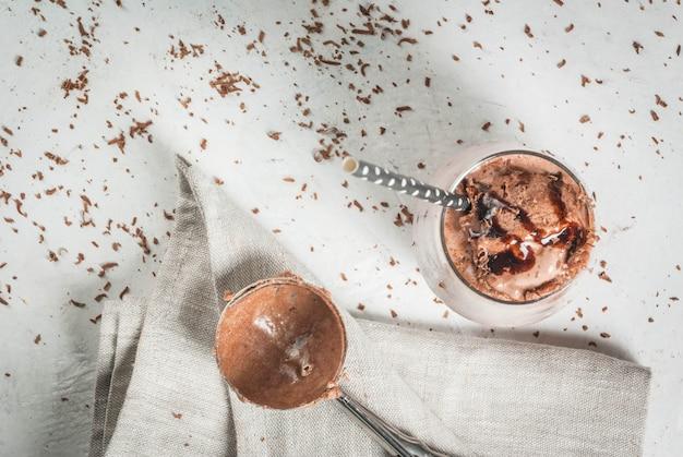 夏の飲み物。チルドアイスチョコレートココア。チョコレートアイスクリーム、チョコレートパウダー、アイススクープ。グラス、飲み用チューブ付き。白いコンクリートのテーブル。上面図