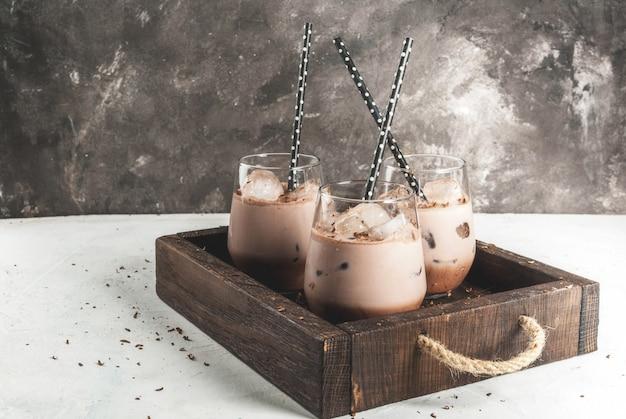 夏の飲み物。チルドアイスチョコレートココア。チョコレートアイスクリーム、チョコレートパウダー、アイススクープ。グラス、飲み用チューブ付き。白いコンクリートテーブル木製トレイ。