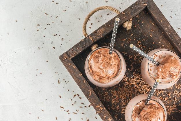 夏の飲み物。チルドアイスチョコレートココア。チョコレートアイスクリーム、チョコレートパウダー、アイススクープ。メガネ、チューブ付き。白いコンクリートテーブル木製トレイ。上面図