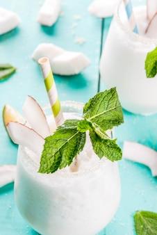 夏の飲み物、カクテル。ライムとミントの冷凍ココナッツモヒート。ピナ・コラーダ。食材と明るい青緑の木製テーブルの上。コピースペースのクローズビュー