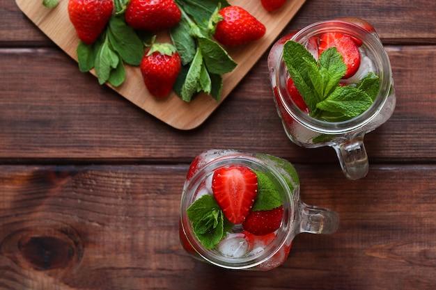 夏の軽食は、木製のテーブルに氷とミントと新鮮なイチゴのレモネードを飲みます