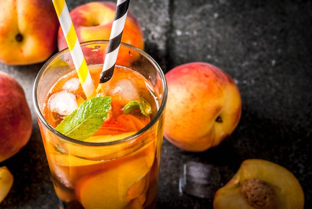 Summer refreshment drinks. iced tea with pieces of organic homemade peach of nectarine. on a black stone background, with ice and ingredients. copyspace close view