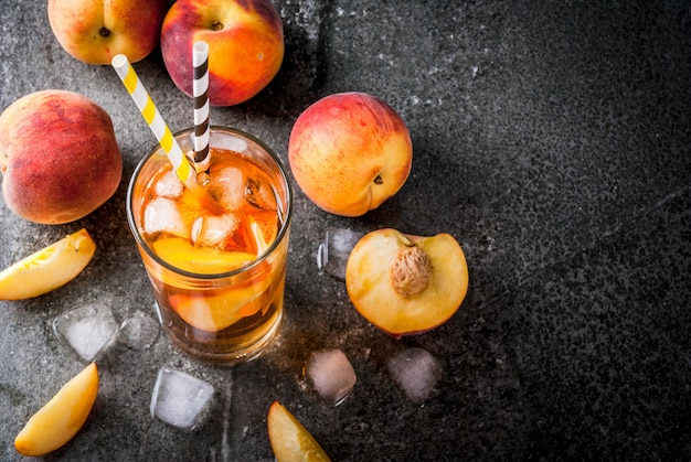 Summer refreshment drinks. iced tea with pieces of organic homemade peach of nectarine. on a black stone background, with ice and ingredients. copyspace top view