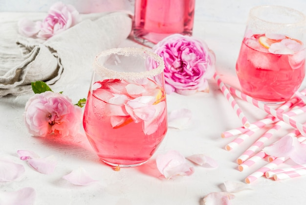 Summer refreshment drinks. light pink rose cocktail, with rose wine, tea rose petals, lemon. on a white stone concrete table. with striped pink tubules, petals and rose flowers.