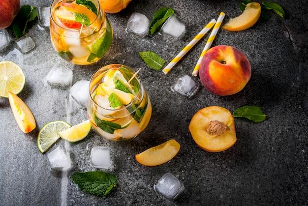 여름 음료수. 라임, 복숭아, 민트와 복숭아 모히토. 어두운 돌 테이블에 재료로. 복사 공간 평면도