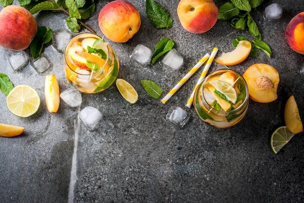 여름 음료수. 라임, 복숭아, 민트와 복숭아 모히토. 어두운 돌 테이블에 재료로. 평면도