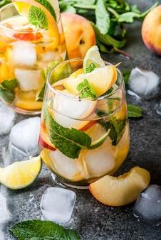 여름 음료수. 라임, 복숭아, 민트와 복숭아 모히토. 어두운 돌 테이블에 재료로.