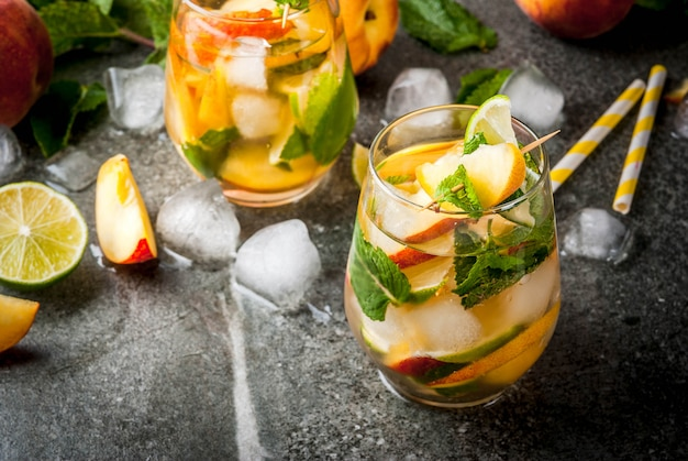 Summer refreshment drinks. peach mojito with lime, peach and mint. with the ingredients on a dark stone table.  copyspace