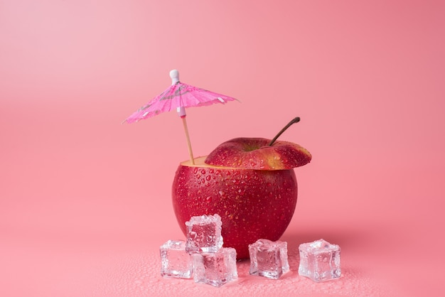 夏のリラックスコンセプト。その中にカクテル傘とピンクの背景に分離された溶ける角氷とカットリンゴのクローズアップ写真