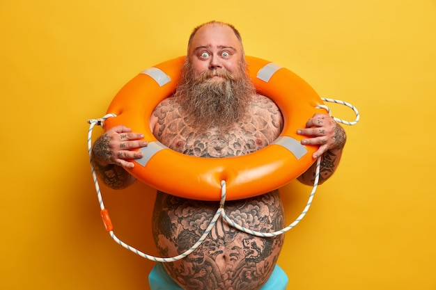 Summer rest and safe swimming concept. shocked bearded stout man stands naked, has tattooed body and big belly, poses with inflated lifebuoy, waits for vacation, isolated over yellow wall