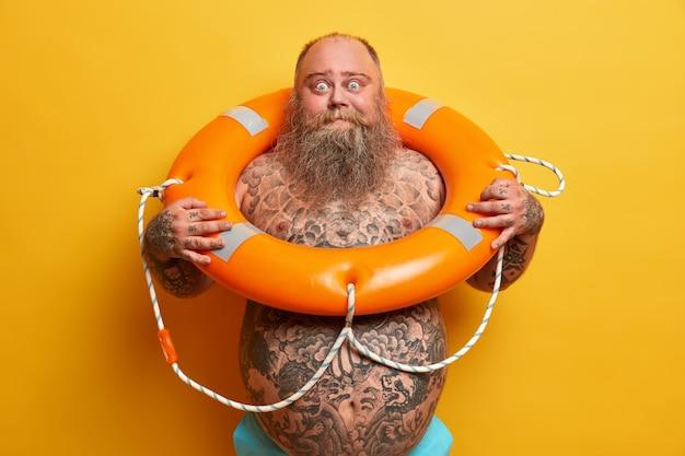 Riposo estivo e concetto di nuoto sicuro. l'uomo robusto e barbuto scioccato sta nudo, ha il corpo tatuato e la grande pancia, posa con il salvagente gonfiato, aspetta le vacanze, isolato sopra il muro giallo