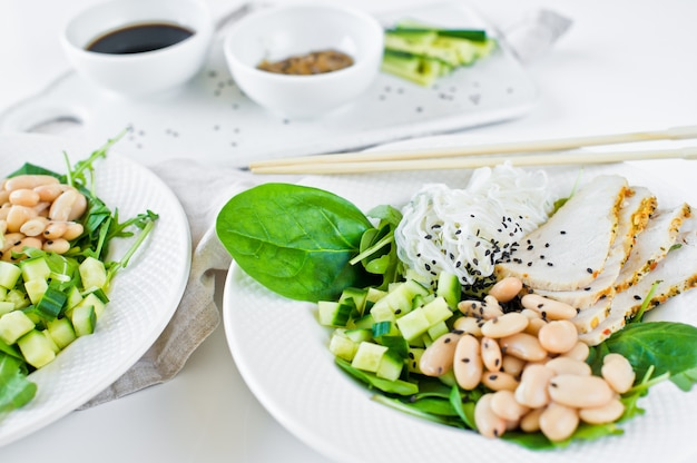Summer restaurant menu, bowl with glass noodles, beans, chicken breast, spinach, arugula and cucumber