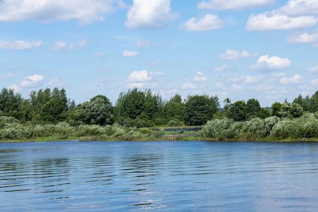 밝은 푸른 하늘과 구름과 여름 강