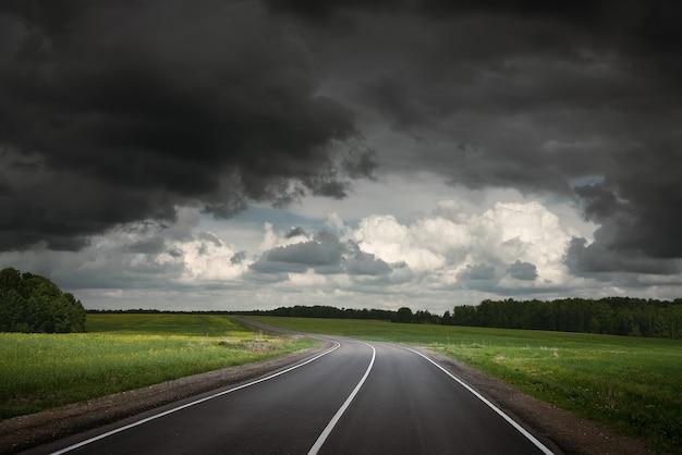 牧草地を通る夏の道劇的な嵐の空