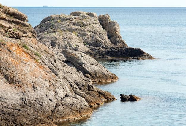 夏の岩の多い海岸線と地平線上の船(「novyjsvit」保護区、クリミア、ウクライナ)。
