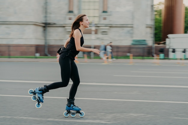 Summer rollerblading and fitness concept. fit young dark haired woman fond of rollerskating exercises all body poses on road along asphalt during sunny day wears comfortable clothes has sporty figure