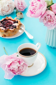 Summer romantic breakfast.cup of coffee,cake,book and peonies.good morning concept.