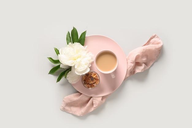 Летний романтический завтрак с чашкой кофе и цветами белых пионов на сером офисном столе