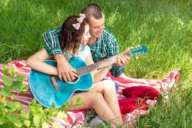 夏のロマンチックなピクニック。男は女の子にギターを弾く方法を示します。草の上に座っているカップル