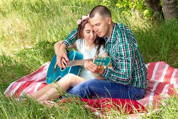 Летний романтический пикник. парень показывает девушке, как играть на гитаре. пара сидит на траве