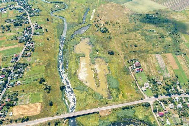 여름 시골 풍경입니다. 조감도. 마을, 강, 녹지 및 도로의 전망